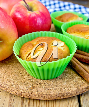 Muffins with apples in silicone molds, cinnamon, napkin on a wooden boards background