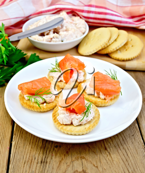 Round crackers with cream, dill and salmon in the plate, napkin, parsley on a wooden boards background