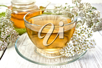 Yarrow tea in a glass cup and teapot, fresh yarrow flowers on a background of light board