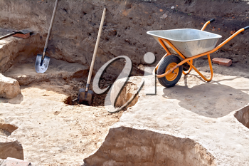 Shovel, wheelbarrow at the site Archaeological excavations on a background of brown soil