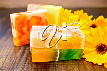 Homemade soap, yellow marigold on a wooden boards background