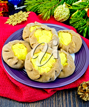 Carols with potato stuffed with rye flour in a plate on a red napkin, Christmas decorations, fir branches on the background of wooden boards