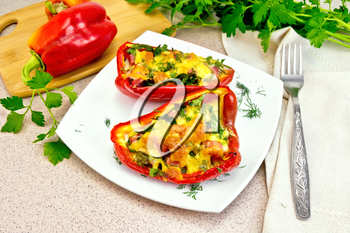 Sweet pepper stuffed with sausage, egg and cheese with dill in white plate, napkin, fork and parsley on table background