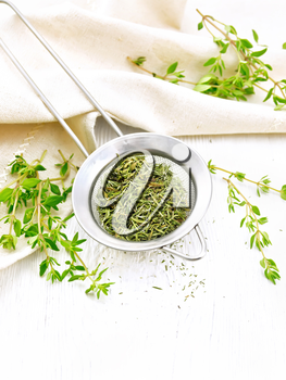 Thyme dry in a metal strainer, fresh greens of grass and linen towel on the background of wooden boards