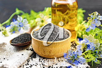 Flour of black caraway in a bowl, seeds in a spoon on burlap, oil in bottle and twigs Nigella sativa with blue flowers and leaves on wooden board background