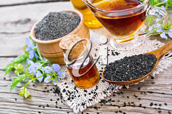 Nigella sativa oil in vial, gravy boat and bottle, seeds in a spoon and black cumin flour in a bowl on burlap, twigs with blue flowers and leaves on background of an old wooden board