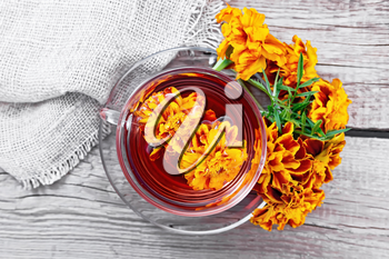 Marigold herbal tea in a glass cup and saucer, fresh flowers, burlap on wooden board background from above