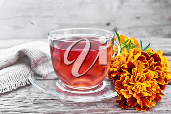 Marigold herbal tea in a glass cup and saucer, fresh flowers, burlap on wooden board background