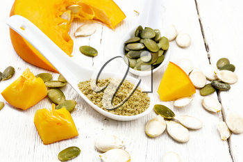 Flour and pumpkin seeds in spoons, slices of vegetable on a background of a light wooden board