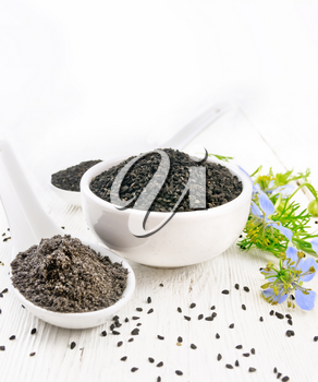 Black cumin seeds in a bowl, flour and seeds in spoons, sprigs of kalingi with blue flowers and green leaves on the background of white wooden board