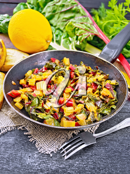 Warm chard salad with orange and onion in an old frying pan on sackcloth, bread, fork on a wooden board background