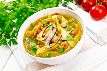 Soup with meat, tomatoes, vegetables, mung bean lentils and noodles in a bowl on a napkin, parsley and spoon on the background of light wooden board