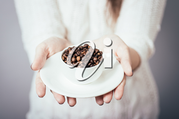 girl holding a cup of coffee beans