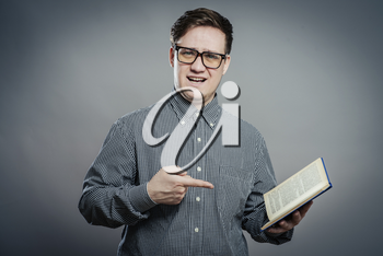 Portrait of young man in glasses reading isolated over grey background
