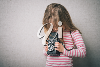 little girl shooting photo with vintage camera