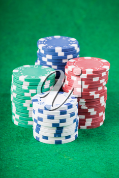 Poker chips on green playing table background