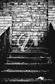 The strange staircase leading into brick wall. Black and white photo in low key