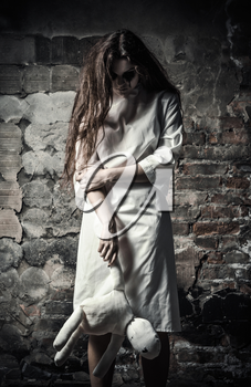 Horror style shot: a scary monster girl with moppet doll in hands