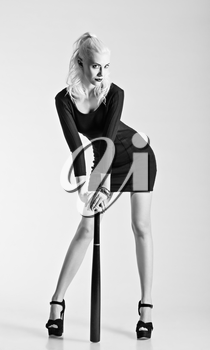 Royalty Free Photo of a Young Woman in a Black Dress Leaning on a Bat