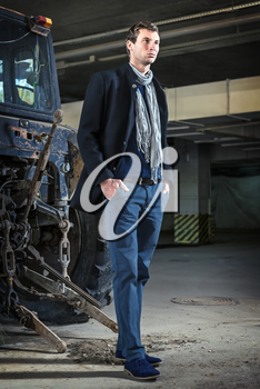 Fashion shot: a handsome young man wearing jeans and coat against the tractor