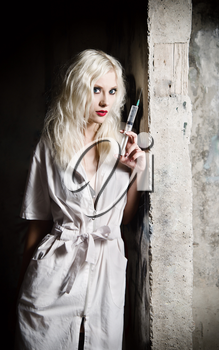 Beautiful young girl in the image of nurse with syringe in hand standing by the wall