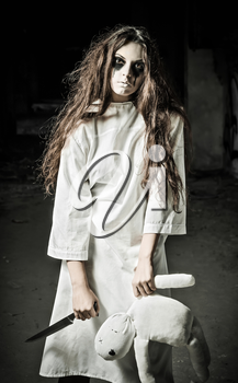 Horror style shot: a strange sad girl with moppet doll and knife in hands