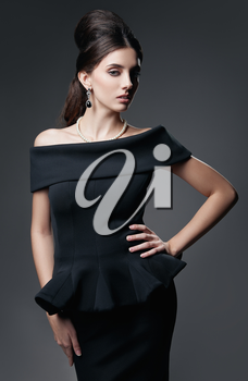 Retro shot: the beautiful young woman in studio. Vintage portrait of lovely girl in 60s style. Aristocratic elegant lady in black dress and pearl necklace against gray background