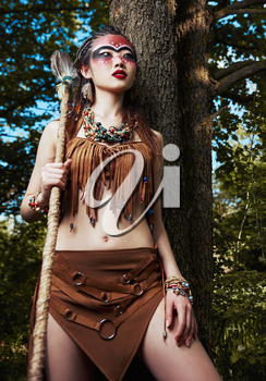 Outdoor portrait of the cute young shamaness (witch doctor) with staff. Beautiful shaman (sorceress) stands at the tree in forest