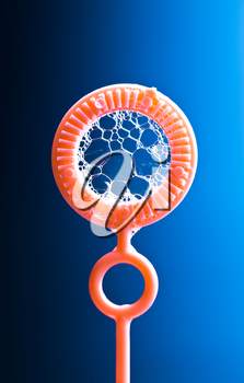 Ring for blowing bubbles, blue background