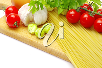 Royalty Free Photo of Pasta and Tomatoes on a Cutting Board