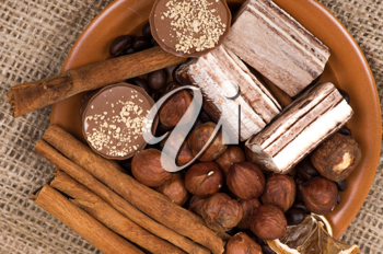 Sweets, cinnamon, nuts and coffee beans on a saucer, on burlap background.
