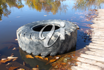 The big old tire from the lorry lies on the bank of beautiful lake in the autumn.