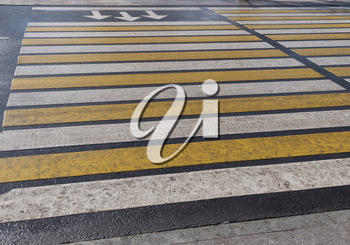 Bright yellow and white stripes of zebra crossing, pedestrian crosswalk.