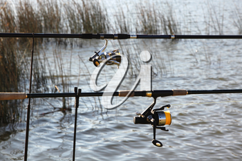 Fishing Rods at Lake with Grass and Rippled Water Background Picture