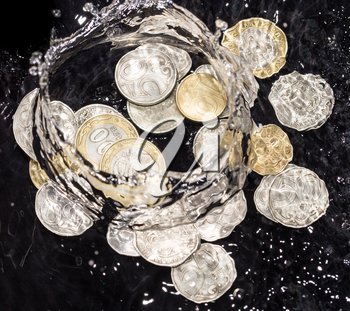 coins in water splashes on a black background