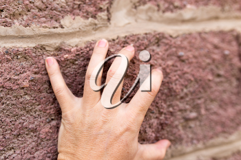 hand on the brick wall