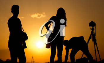Silhouette of the girl and the man of the photographer at sunset .