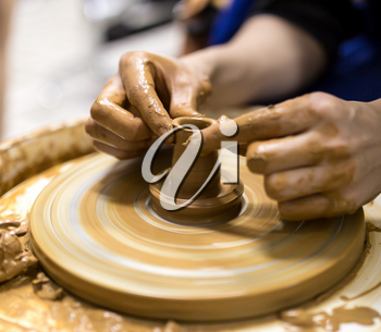 The master makes by hands the product of dishes from clay
