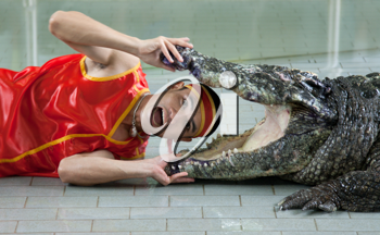 Royalty Free Photo of a Man Holding a Crocodile's Mouth Open