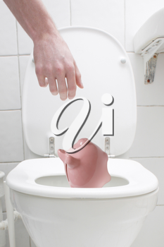 Royalty Free Photo of a Man Throwing a Piggy Bank in the Toilet