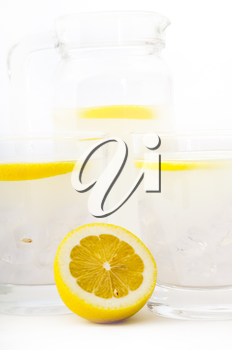 fresh lemonade drink with lemon slice closeup and pitcher carafe