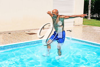 Royalty Free Photo of a Man Jumping into a Swimming Pool