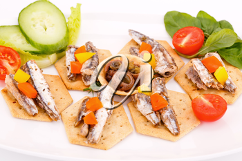 Fish and peppers on crackers with vegetables on white plate.
