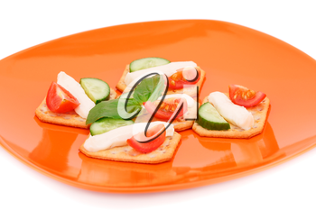 Crackers with fresh vegetables and cream on orange plate.
