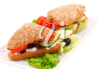 Sandwiches with fresh vegetables and cheese on plate.