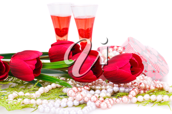 Two glasses, flowers, colorful pearls necklaces and gift box on white background.