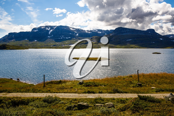 Landscape with mountains, lake, sky and clouds in Norway.
