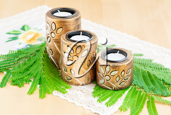Three brown ancient style candle nests and green leaves on cloth.