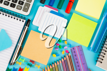Back to school, stationary on blue background.