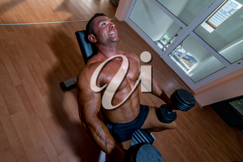male bodybuilder resting after doing heavy weight exercise